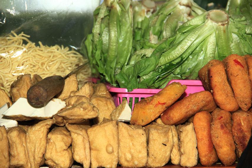 Tahu campur terbuat dari bahan-bahan seperti, daging sapi kenyal, tahu goreng, taoge, selada air, mie kuning